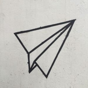 Paper airplane on concrete
